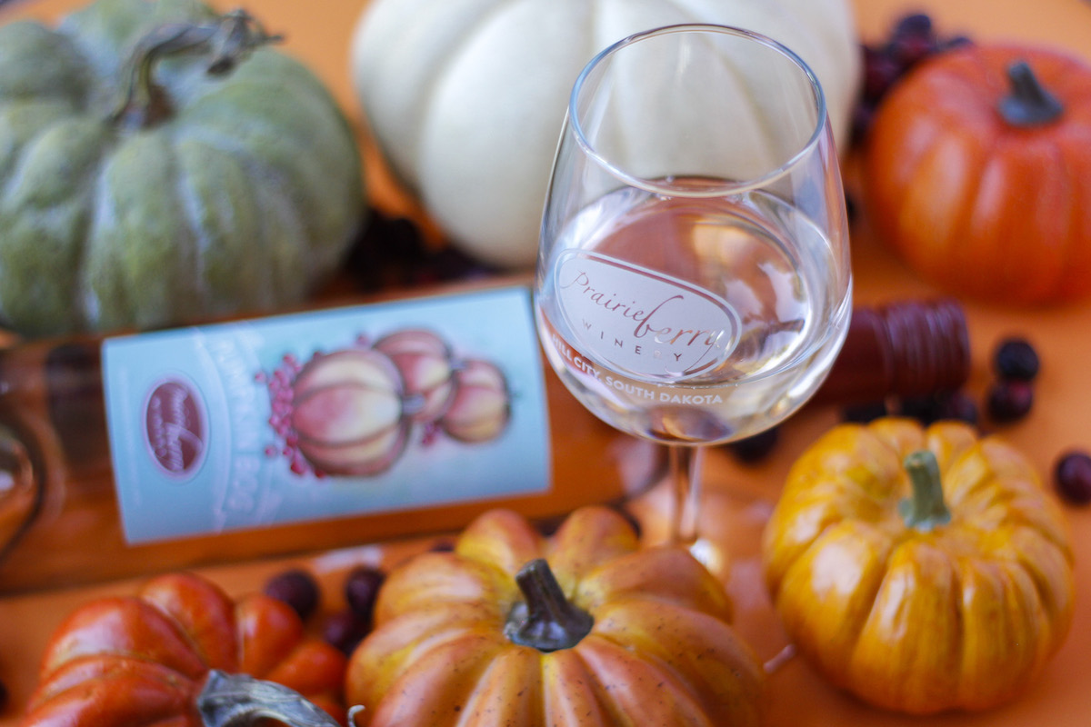 A festive fall scene featuring a glass of Pumpkin Bog wine, made in South Dakota by Prairie Berry Winery